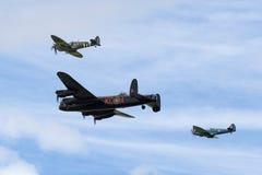 在形成的英国皇家空军不列颠战役纪念飞行Avro兰卡斯特轰炸机PA474飞行与两个Supermarine烈性人 免版税库存照片