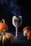 在形状的玻璃有万圣夜饮料的一块头骨 免版税图库摄影