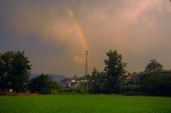 在彩虹下的一个田园诗村庄 免版税库存图片