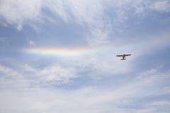 在彩虹下的单引擎飞机 库存图片