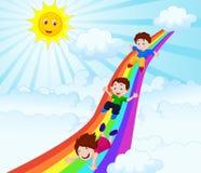 滑在彩虹下的孩子 免版税库存图片