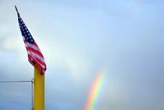 在彩虹前面的US/American旗子老荣耀 库存图片