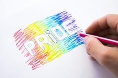 在彩虹的颜色绘的题字自豪感 天同性恋者 自豪感月 免版税库存照片