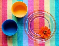 在彩虹placemat的五颜六色的盘与花 图库摄影