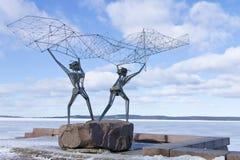 在彼得罗扎沃茨克,俄罗斯雕刻奥涅加湖的堤防的渔夫 免版税图库摄影