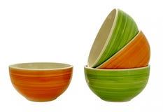 在彼此堆积的绿色和橙色碗,形成小瀑布 库存图片