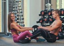 在彼此对面坐地板和做胃肠咬嚼的年轻有吸引力的运动的夫妇在健身中心 库存照片