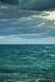在很远海的天际是红色小船 库存图片