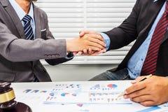在律师和一个男性办公室工作者之间的握手 免版税图库摄影