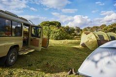 在徒步旅行队卡车附近的白色和绿色生动的帐篷在Moutain campsi 免版税库存图片