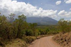 在徒步旅行队的多灰尘的路在坦桑尼亚 库存图片
