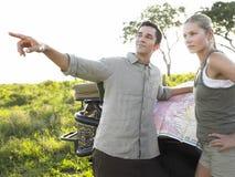 在徒步旅行队的年轻夫妇与地图 库存照片