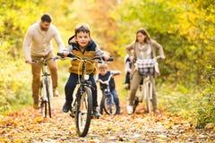 在循环在秋天公园的温暖的衣裳的年轻家庭 库存照片