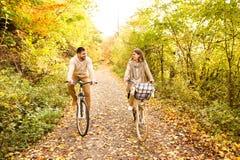 在循环在秋天的温暖的衣裳的年轻夫妇停放 免版税库存照片