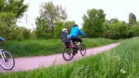 在循环在绿园的自行车的愉快的家庭 影视素材