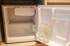 在微型冰箱里面在有水瓶的旅馆卧室 免版税库存图片