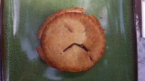 在微型樱桃饼的哀伤的面孔在一块绿色板材 免版税库存图片