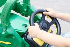 在微型汽车舵的小女孩手  图库摄影