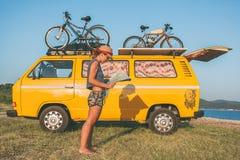 在微型货车汽车前面的年轻嬉皮妇女在海滩 库存图片