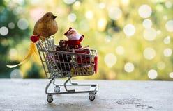 在微型购物车或台车的圣诞节装饰项目反对被弄脏的自然黄色和绿色背景 圣诞节和新 免版税库存图片