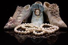 在微型鞋子前面的珍珠项链 免版税库存图片