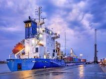 在微明与剧烈的云彩,安特卫普,比利时港的集装箱船  免版税库存照片