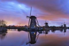 在微明的风车在著名kinderdijk的日落,荷兰以后 免版税库存照片
