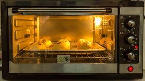 在微波炉前面的被烘烤的小圆面包 免版税库存照片