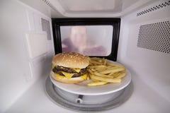 在微波的准备食物 板材用汉堡包和油炸物里面烤箱 库存照片