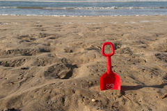 在微笑对热带海滩的沙子的红色海滩玩具 免版税库存照片