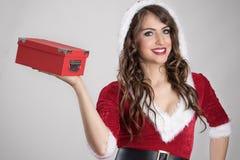 在微笑对照相机的红色箱子的圣诞老人帮手少妇运载的圣诞节礼物 库存照片