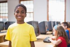 在微笑对照相机的计算机类的逗人喜爱的学生 免版税库存照片