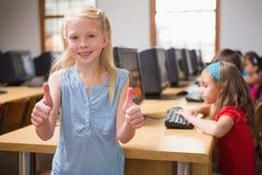 在微笑对照相机的计算机类的逗人喜爱的学生 图库摄影