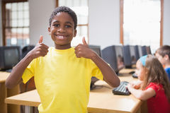 在微笑对照相机的计算机类的逗人喜爱的学生 库存照片