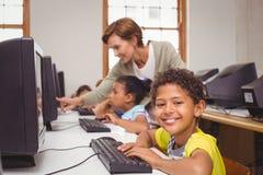在微笑对照相机的计算机类的逗人喜爱的学生 免版税库存图片