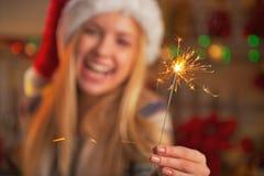 在微笑的十几岁的女孩的特写镜头拿着闪烁发光物的圣诞老人帽子的 库存照片