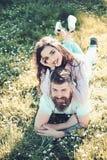 在微笑的夫妇面对抽烟户外,在背景的自然 放置在草春日的男人和妇女 抽烟嗜好 库存图片