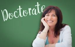 在微笑的妇女后的绿色黑板写的博士学位 免版税库存图片