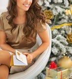 在微笑的少妇和圣诞节明信片的特写镜头 免版税库存照片