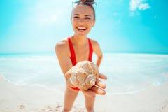 在微笑的年轻女人的特写镜头海岸陈列海壳的 库存照片
