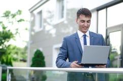 在微笑的白色的背景生意人查出的膝上型计算机 图库摄影