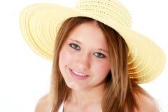 在微笑的青少年的空白黄色的美丽的帽子 免版税图库摄影