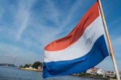 在微风的荷兰红色,白色和蓝色镶边旗子在蟒蛇船尾  库存图片