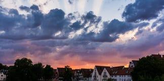 在德国村庄乌尔姆的深刻的灼烧的红色紫色蓝色光芒日落 库存图片