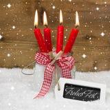 在德语的圣诞快乐与四个红色蜡烛 免版税库存照片