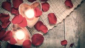 在心形的烛台的两个被启迪的蜡烛与上升了 库存图片