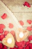 在心形的烛台的两个被启迪的蜡烛与上升了 免版税库存照片