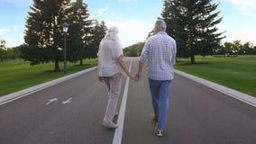 在心脏夫妇的年轻人在户外快乐的步行 股票录像