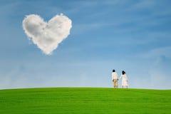在心脏形状云彩下的夫妇 免版税库存照片