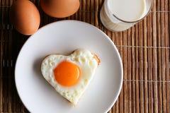 在心脏形状和牛奶顶视图的煎蛋 库存照片